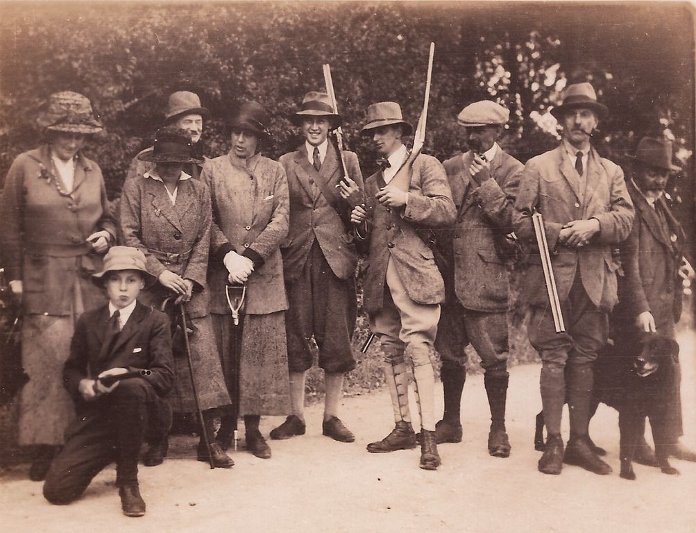 A hunting group with shotguns and a dog