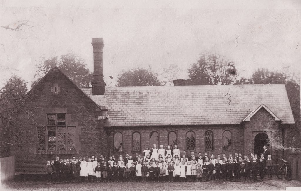 A class outside the school showing the school building